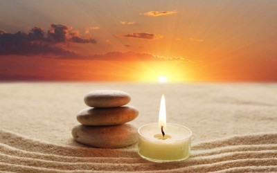 candle and stones on sand